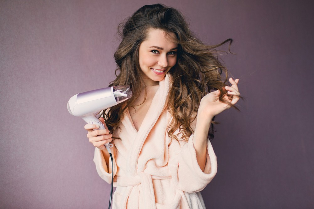 femme aux cheveux long se séchant les cheveux en peignoir