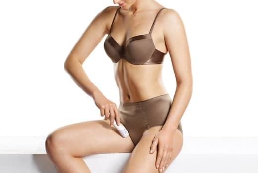 Jeune femme utilisant une tondeuse bikini