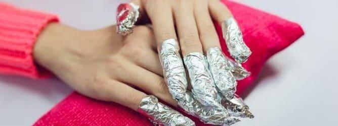 mains de femmes avec les doigts enroulés d'aluminium pour la pose du vernis semi-permanent