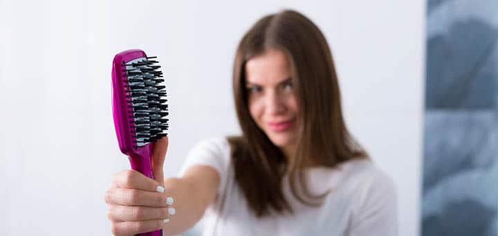 femme tenant une brosse lissante philips